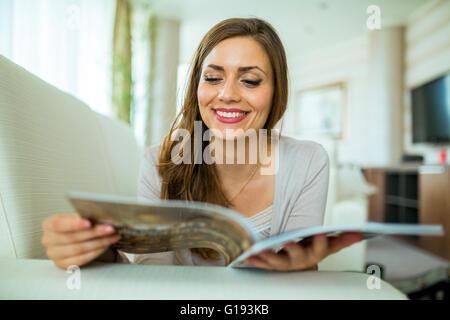 Belle femme sur un canapé-lit un document dans un élégant salon bien éclairé Banque D'Images