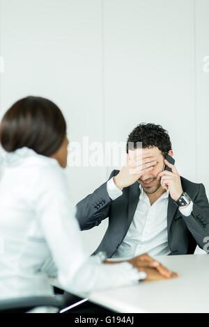 Businessman recevoir de mauvaises nouvelles sur le téléphone ayant un mal de tête sur les problèmes Banque D'Images