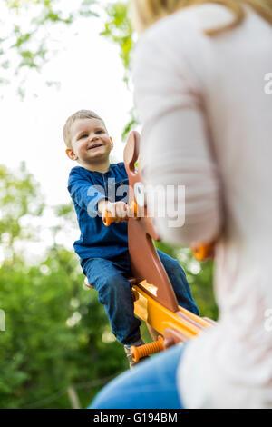 Beau petit garçon se balançant avec sa mère Banque D'Images