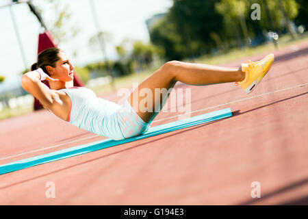 Belle jeune femme exerçant à l'extérieur en faisant des abdominaux Banque D'Images