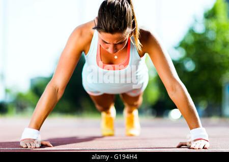 L'accent young Beautiful woman faisant push-ups à l'extérieur sur une chaude journée d'été