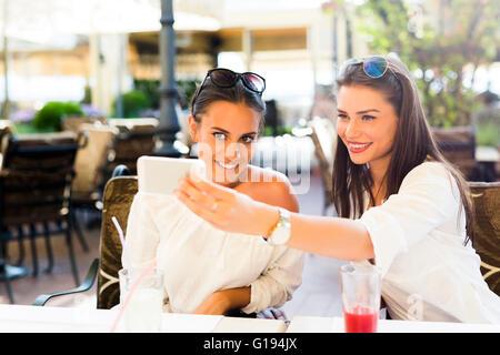 Deux belles jeunes femmes prenant une des selfies eux-mêmes pendant la pause déjeuner Banque D'Images