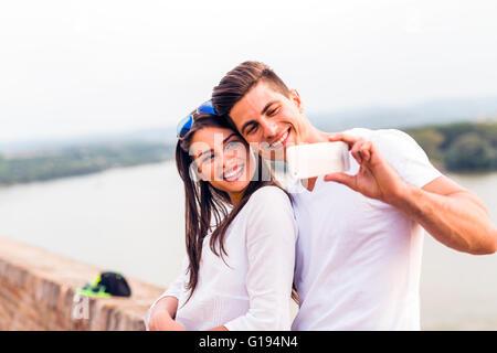 Jeune beau couple en tenant une de selfies eux-mêmes et d'être heureux