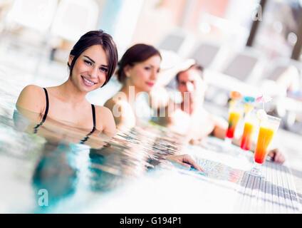 Les jeunes boivent des cocktails au bord de la piscine et se détendre Banque D'Images