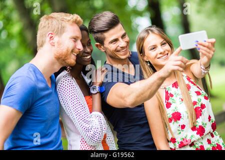 Groupe de jeunes et des couples en tenant vos autoportraits en nature et smiling Banque D'Images