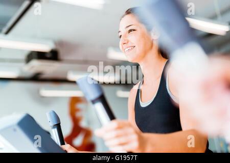 Belle jeune fille à l'aide de l'entraîneur elliptique dans une salle de sport dans un esprit positif Banque D'Images