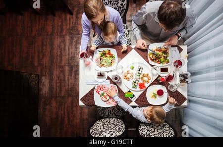 Famille de quatre personnes ayant délicieux repas dans un restaurant Banque D'Images