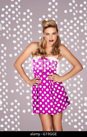 Belle blonde modèle mode rétro dans une robe à pois rose posant devant un fond de studio avec des points Banque D'Images