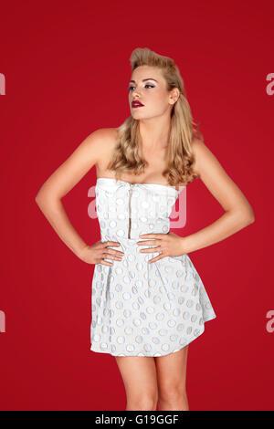 Belle blonde rétro mannequin pose dans une élégante jupe blanc contre un riche fond studio rouge Banque D'Images