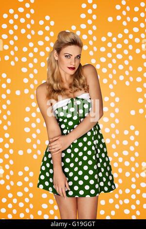Modèle superbe blonde en mode rétro portant une minijupe à pois vert dress posing devant un studio tachetée jaune Banque D'Images