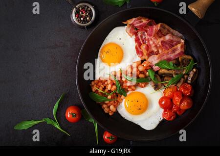 Petit-déjeuner anglais - œuf frit, haricots, tomates, champignons, du bacon et des toasts. Vue d'en haut Banque D'Images