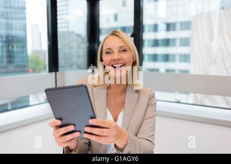 Happy Middle aged business woman using digital tablet. Arrière-plan de bureau moderne Banque D'Images