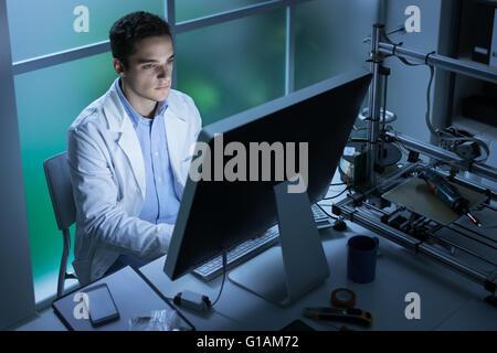 Certain élève ingénieur travaillant dans le laboratoire et à l'aide d'un ordinateur, l'imprimante 3D à l'arrière Banque D'Images
