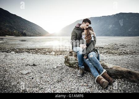 Jeune couple ayant une date romantique au bord du lac, ils sont hugging et assis sur un tronc sur la plage, l'amour Banque D'Images