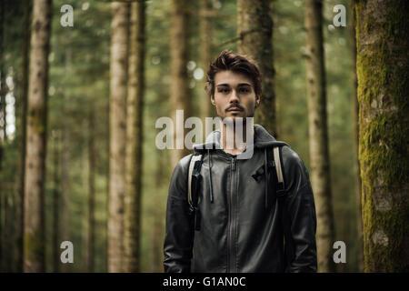 Jeune homme séduisant explorer une forêt, il est looking at camera Banque D'Images