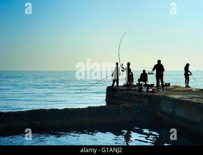 Groupe de pêcheurs sur une jetée au coucher du soleil. La péninsule de Crimée Banque D'Images