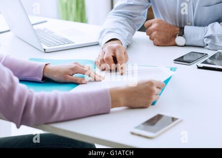 Jeune femme ayant une réunion d'affaires avec un comité exécutif dans son bureau, il se dirige sur un contrat et Banque D'Images