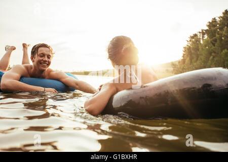 Young couple flottant sur les chambres à air dans l'eau. Jeune homme et femme dans un tube gonflable dans un lac sur une journée ensoleillée.