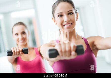 Teen sporty girls à l'exercice de gymnastique et l'haltérophilie à l'aide d'haltères, soins du corps et le concept Banque D'Images