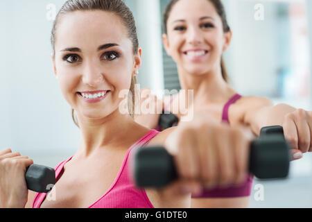 Les jeunes femmes gaies de l'exercice à la salle de sport et de l'haltérophilie à l'aide d'haltères courtes, elles Banque D'Images