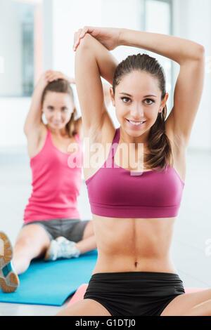 Les jeunes femmes dans la salle de sport assis sur un tapis et de faire des exercices d'étirement pour des bras Banque D'Images