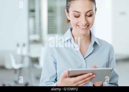 Young smiling business woman en utilisant un écran tactile numérique et utiliser des applications, il est debout Banque D'Images