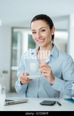 Jeune femme tenant une tasse de café et d'avoir une pause assis au bureau 24