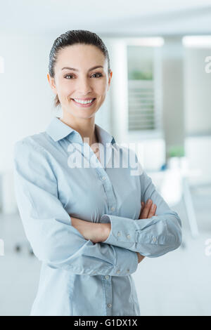 Beau confident business woman posing with crossed arms, smiling at camera et debout dans son bureau Banque D'Images