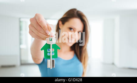 Belle smiling woman holding clés de maison de sa nouvelle maison, immobilier et déménagement concept Banque D'Images