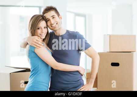 Young happy couple hugging in their new house and smiling at camera Banque D'Images