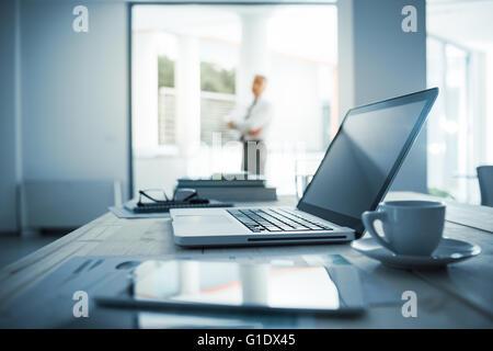 Businessman standing with arms crossed dans son bureau, ordinateur de bureau avec ordinateur portable en premier Banque D'Images