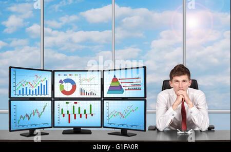 Assis près de trader trading station qui se compose de quatre écrans avec des données financières. Banque D'Images