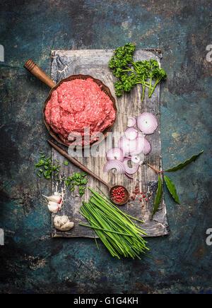 La viande hachée dans une poêle dans la cuisson des ingrédients et cuillère en bois sombre sur fond rustique, vue Banque D'Images