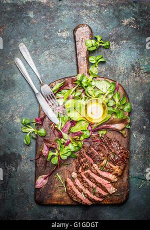 Meubles à point boeuf grillé Steak barbecue servi avec de la salade verte et des couverts sur la planche à découper Banque D'Images