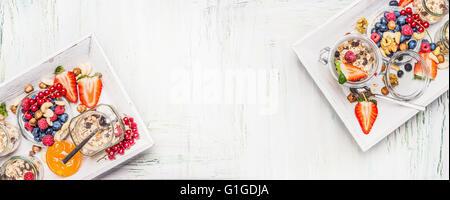 Petit-déjeuner sain ingrédients: Muesli en pot avec les baies fraîches, graines et noix sur fond de bois clair, Banque D'Images