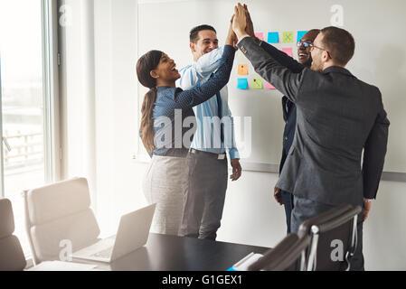 L'équipe commerciale réussie multiraciale diversifié offrant un bon geste fives alors qu'ils célèbrent dans une Banque D'Images