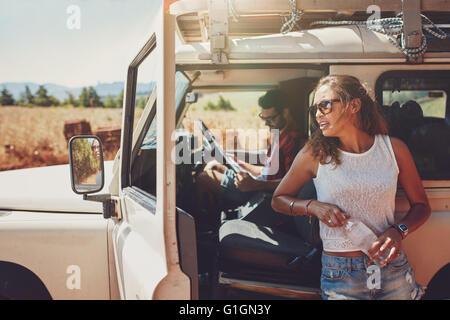 Jeune femme debout à l'extérieur de la voiture tenant une bouteille d'eau à l'homme assis sur le siège du conducteur Banque D'Images