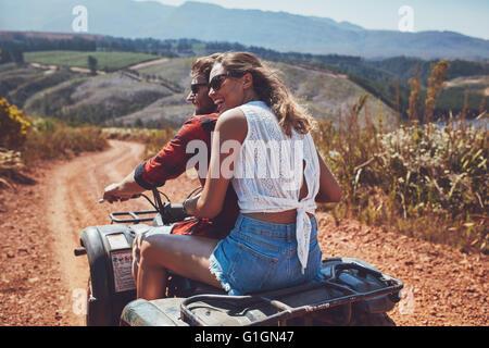 Vue arrière shot of young couple riding sur un quad en campagne et à la voiture en souriant. Femme assise derrière Banque D'Images