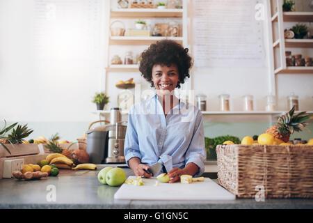 Portrait de belle jeune femme africaine debout derrière le comptoir du bar et à couper les fruits frais. Femme travaillant au bar à jus.