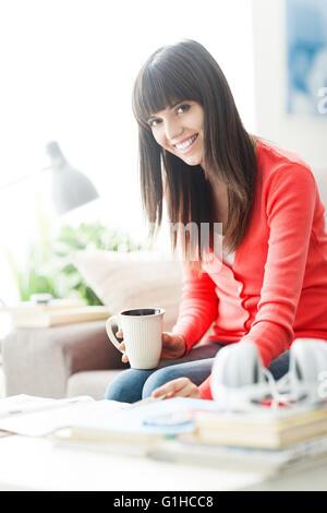 Attractive young woman relaxing at home, elle est assise sur le canapé, la lecture d'un magazine et d'avoir un café