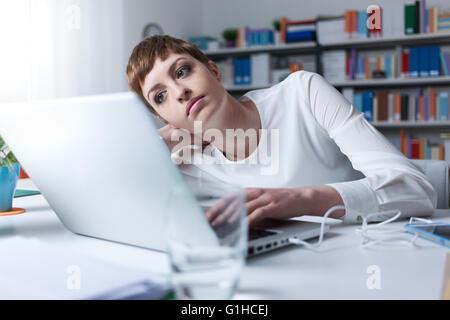 Femme fatiguée dans le bureau s'appuyant sur sa main en utilisant un ordinateur portable Banque D'Images