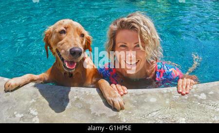 Funny portrait of smiling woman Playing with dog et de formation chiot golden retriever en bleu piscine. Banque D'Images