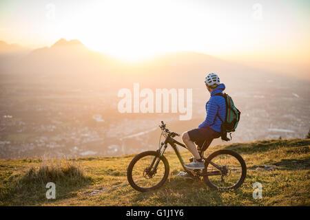 Man on mountain bike à la vue au coucher du soleil, Salzbourg, Autriche Banque D'Images