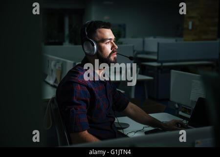 Beau jeune homme concentré dans les écouteurs assis et travaillant de nuit dans le bureau sombre Banque D'Images