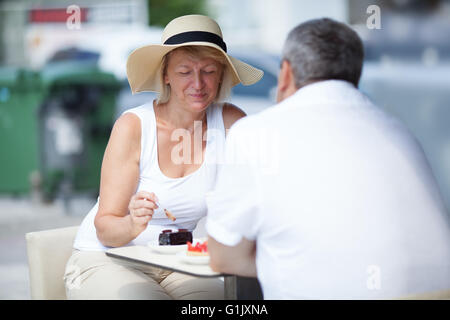 Vieux couple eating in outdoor cafe Banque D'Images