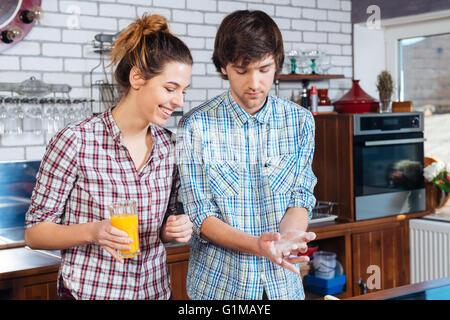 Beau jeune couple drinking orange juice et la cuisson à l'aide de la farine dans la cuisine Banque D'Images