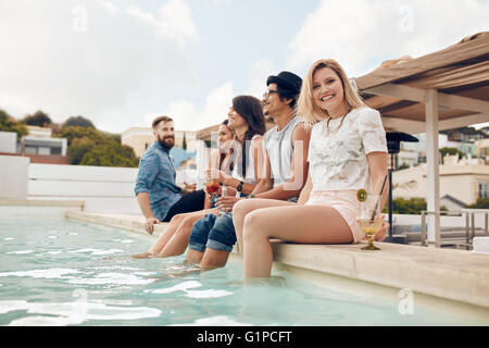 Portrait de jeune femme assise au bord de la piscine avec ses amis à faire la fête. Les jeunes à vous détendre au Banque D'Images