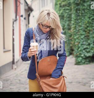 Femme à la recherche de trucs dans son sac à main. Banque D'Images
