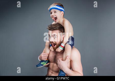 Gros plan du père et son petit-fils s'amusant et en criant sur fond gris Banque D'Images