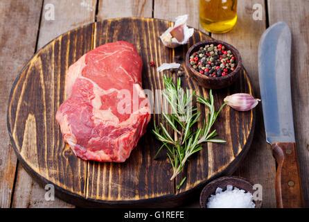 La viande fraîche de boeuf cru avec du sel et le poivre, le romarin et les tomates sur une planche à découper sur Banque D'Images